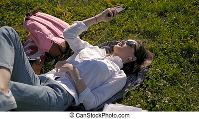 Beautiful Young Woman Laying on The Grass And Listening To Music. Making Selfie.