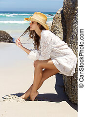 Beautiful young woman leaning against rock at the beach