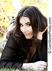 Beautiful young woman lies on green grass