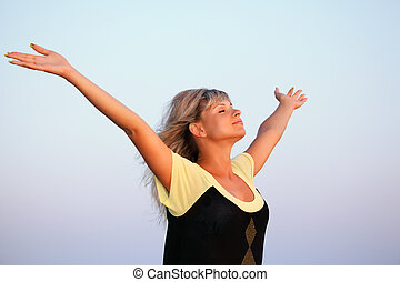 beautiful young woman lifted hands upwards against sky