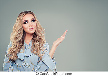 Beautiful young woman looking and pointing up on background with copy space