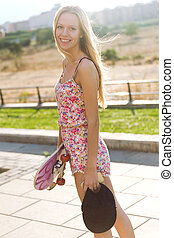 Beautiful young woman looking at camera with skateboard.