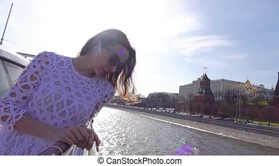 Beautiful young woman looking at Moscow Kremlin from river tour boat. Slow motion video
