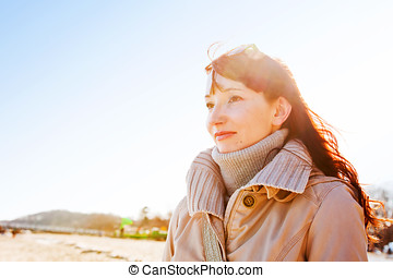 Beautiful young woman looking at the sky, sunny day.