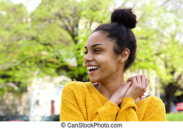 Beautiful young woman looking away and laughing