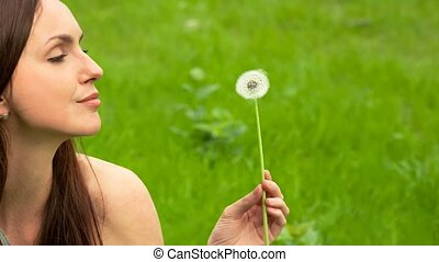 Beautiful Young Woman Looking on Dandelion in her hand