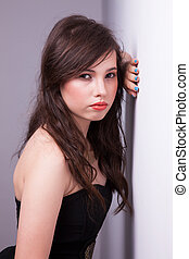 beautiful young woman, looking to camera, against the wall, studio shot