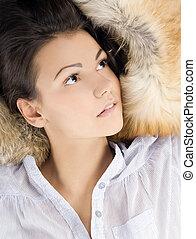 beautiful young woman lying in a fur