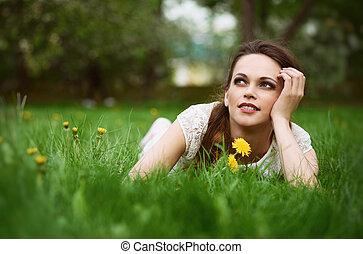 Beautiful young woman lying in green grass