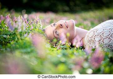 Beautiful young woman lying in meadow of flowers