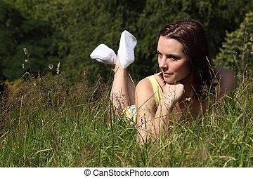 Beautiful young woman lying in countryside grass - Beautiful...