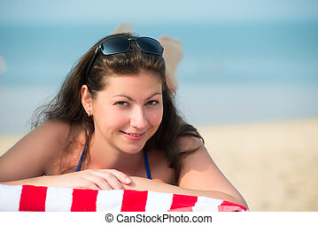 beautiful young woman lying on a lounger near the sea