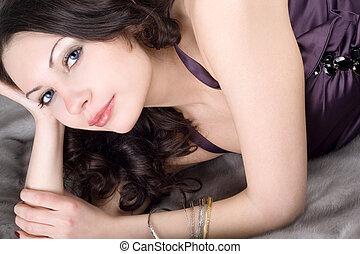 Beautiful young woman lying on grey fur coat