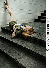 Beautiful young woman lying on ground
