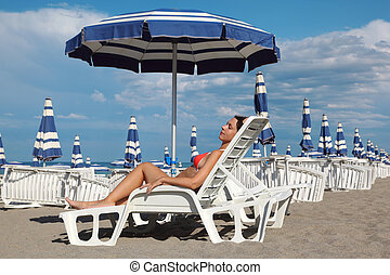 beautiful young woman lying on lounger under beach umbrella and sunbathe. in background rows of white loungers and blue umbrellas