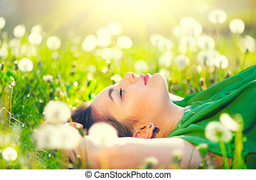 Beautiful young woman lying on the field in green grass and dandelions