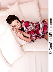 Beautiful young woman lying on the sofa