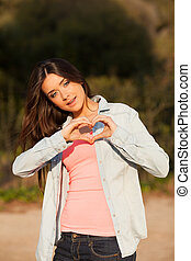 young woman makes heart shape with hands