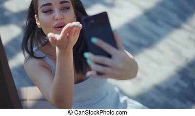 Beautiful young woman making selfie in the park