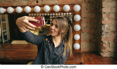 Beautiful young woman making selfie portrait on a smartphone in dressing room indoors
