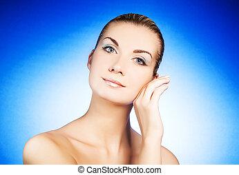 Beautiful young woman massaging her face