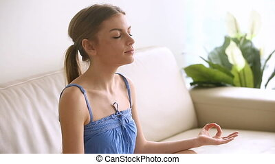 Beautiful young woman meditating at home, breathing air, practicing yoga