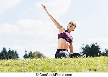 woman meditating on grass field