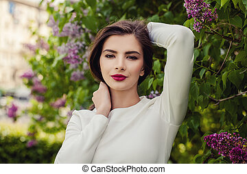 Beautiful young woman model brunette with lilac flowers
