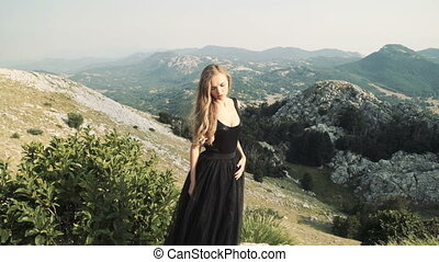 beautiful young woman model in a black fluffy elegant long dress posing on the camera in the background of a mountain landscape.