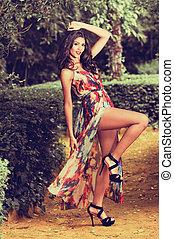 Beautiful young woman, model of fashion, in a garden