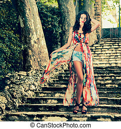 Beautiful young woman, model of fashion, in a garden stairs