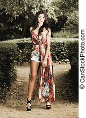 Beautiful young woman, model of fashion, in a garden
