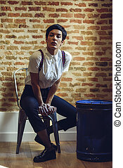 Beautiful young woman, model of fashion, with very short haircut, looking at camera sitting on chair, with a brick wall in the background.