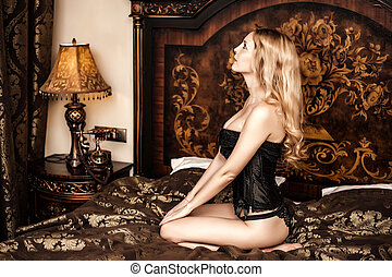 Beautiful young woman model sitting on vintage bed