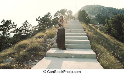 beautiful young woman model with long hair in a black fluffy elegant long dress is walking along the balcony in the background of a mountain landscape. summer view of the mountains.