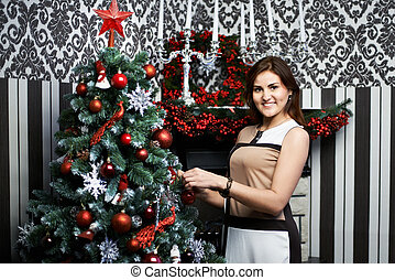 Beautiful young woman near holiday Christmas tree