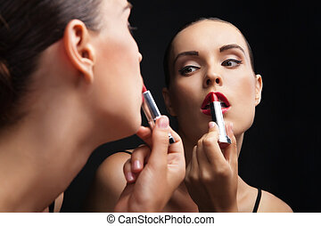Beautiful young woman near mirror with lipstick