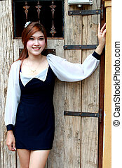 Beautiful young woman near old wooden door