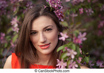 beautiful young woman near the blossoming spring tree