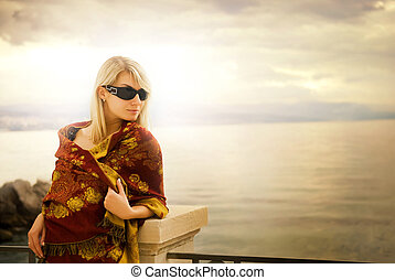 Beautiful young woman near the ocean at sunset