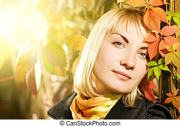 Beautiful young woman on autumn background