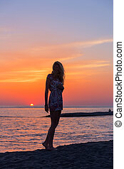 Beautiful young woman on beach at sunset