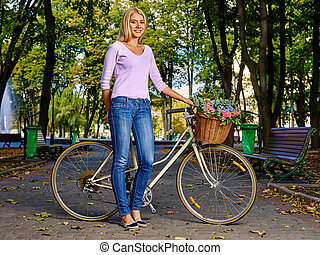 Beautiful young woman on bike in autumn park.