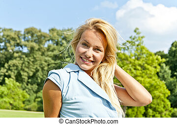 Beautiful young woman on green loawn in park playing her hair an