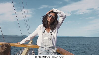 Beautiful young woman on ship. Pretty girl on ship in summer time. luxury woman yachting in sea at sunset. Sea waves
