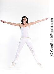 beautiful young woman on studio isolated white background doing her workout stretch jump happy