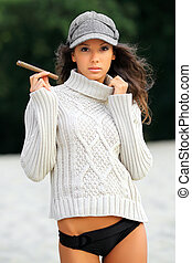 beautiful young woman on the beach with a cigar