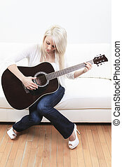 beautiful young woman on the couch with a guitar