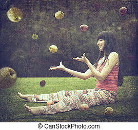 Beautiful young woman on the green meadow with apples