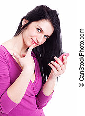 beautiful young woman on the phone, smiling at the camera with one finger to touch the mouth